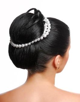 Retrovisor de um penteado de casamento moderno e elegante com pérolas isoladas em branco