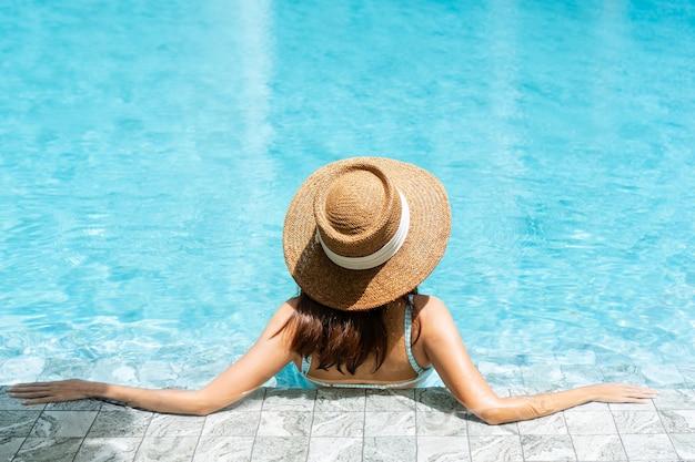Retrovisor de uma atraente mulher asiática de biquíni e chapéu de palha relaxando em uma piscina luxuosa