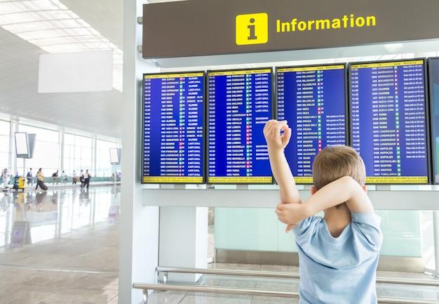Retrovisor de uma criança entediada, cruzando os braços e olhando o painel de horários de voos no aeroporto