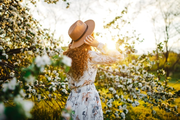 Retrovisor de uma jovem entre as flores brancas das macieiras no parque primavera. mulher usando vestido branco e chapéu bege, sentindo-se revigorada e goza de bom tempo no pôr do sol. conceito de temporada.
