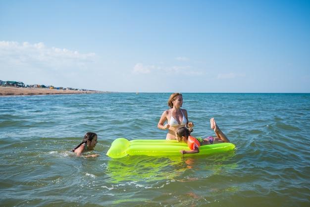 Retrovisor de uma jovem mãe de família positiva e duas filhas pequenas nadando em um colchão de ar amarelo