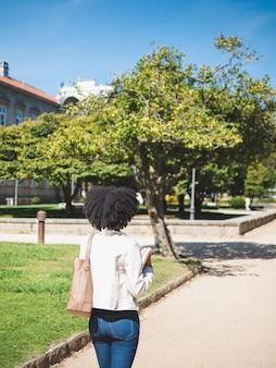 Retrovisor de uma jovem negra, com cabelos cacheados, segurando alguns livros, do lado de fora