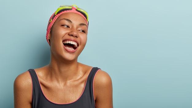 Retrovisor de uma mergulhadora positiva em traje de banho, expressa emoções positivas, ri alto, molha o corpo depois de mergulhar na água, desfruta da aula de aeróbica aquática isolada na parede azul, espaço em branco
