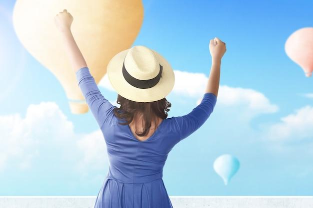 Retrovisor de uma mulher asiática com chapéu olhando para um balão de ar colorido voando com o fundo do céu azul