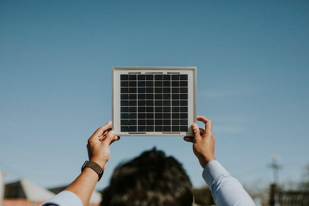 Retrovisor de uma mulher ecológica segurando um painel solar no céu Foto Premium