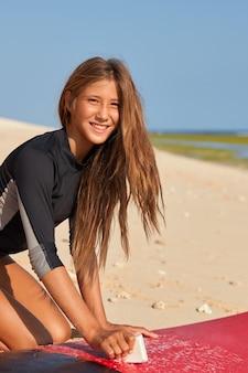 Retrovisor de uma mulher muito sorridente, vestida com roupa de mergulho preta