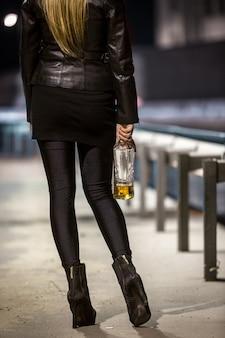 Retrovisor de uma mulher posando na rua com uma garrafa de uísque