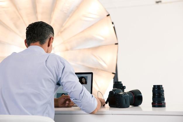 Retrovisor do fotógrafo usando o laptop em seu local de trabalho