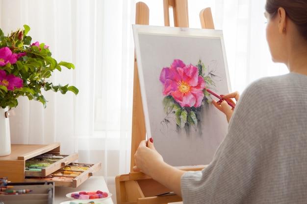 Retrovisor do jovem artista pinta o esboço de peônias rosa de uma caixa com lápis de cor pastel secos em seu estúdio enquanto está sentado em um cavalete de madeira ao ar livre. conceito de criatividade e hobby. tons rosa.