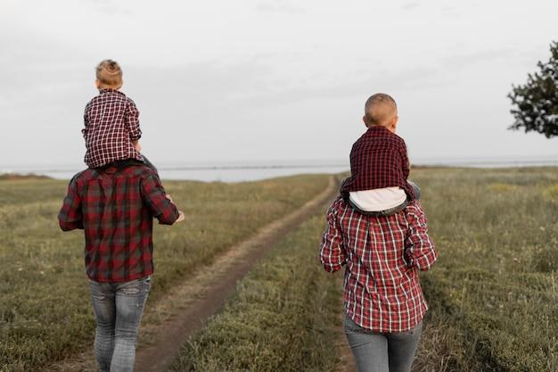 Retrovisor, família feliz caminhando na natureza