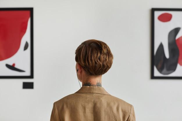 Retrovisor gráfico de uma jovem mulher tatuada olhando pinturas e ouvindo guia de áudio na exposição da galeria de arte moderna,