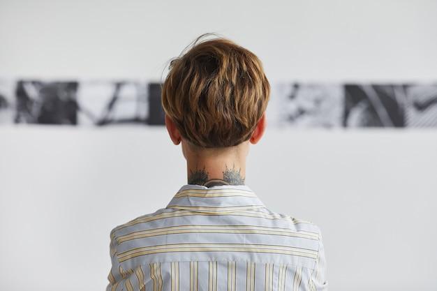 Retrovisor gráfico de uma jovem mulher tatuada olhando pinturas em uma exposição de arte contemporânea,
