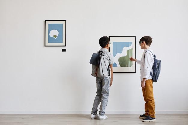 Retrovisor mínimo de dois alunos olhando pinturas abstratas na galeria de arte moderna, copie o espaço