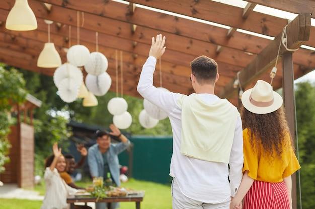 Retrovisor retrato de um jovem casal acenando para amigos enquanto sai da festa ao ar livre no verão