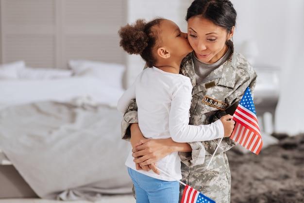 Reunião apaixonada. criança doce e terna dando as boas-vindas à sua mãe em casa depois de sentir sua falta por alguns dias, enquanto segura uma bandeira