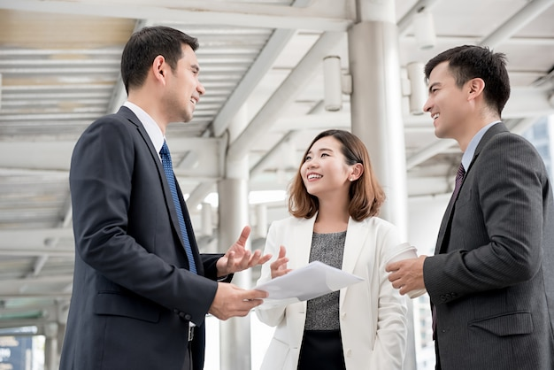 Reunião asiática feliz do sócio fora do escritório que discute o trabalho