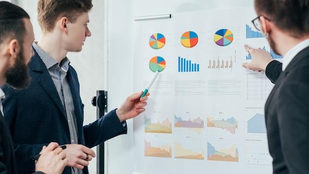 Reunião corporativa. análise de negócio. brainstorming e trabalho em equipe. colegas do sexo masculino trabalhando com gráficos no quadro branco.