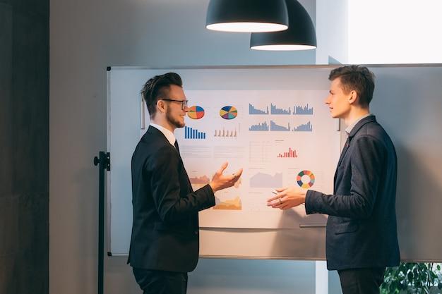Reunião corporativa. dois jovens em pé no quadro branco com gráficos, discutindo a estratégia de negócios de inicialização.