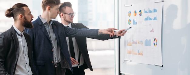Reunião corporativa. planejamento da estratégia de negócios. brainstorming e trabalho em equipe. colegas do sexo masculino discutindo o projeto na sala de conferências.