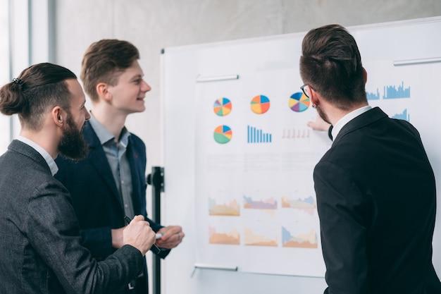 Reunião corporativa, trabalho em equipe. homens de negócios jovens trabalhando com gráficos no quadro branco.