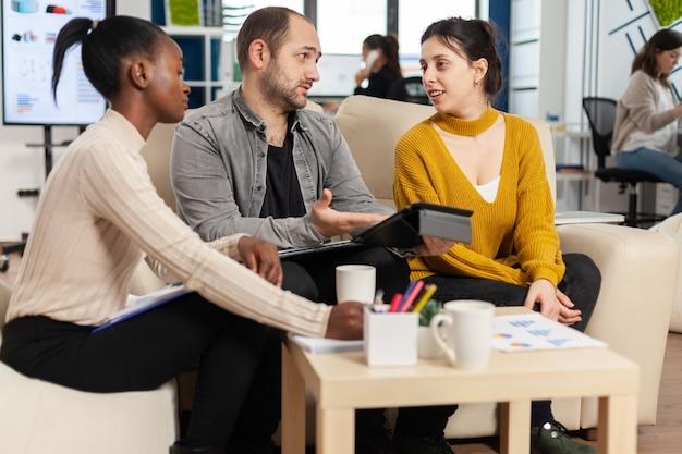 Reunião da equipe de inicialização com o líder da empresa apontando a estratégia em relatórios financeiros