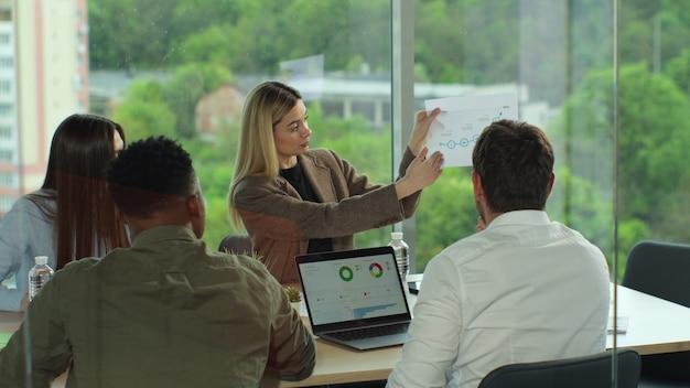 Reunião da equipe de negócios em um escritório moderno grupo de raça mista de jovens discutindo ideias de inicialização, empresários trabalhando e se comunicando na mesa do escritório