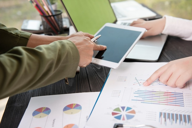 Reunião da equipe de negócios para discutir dados estatísticos apresentados na forma de gráficos e tabelas digitais.