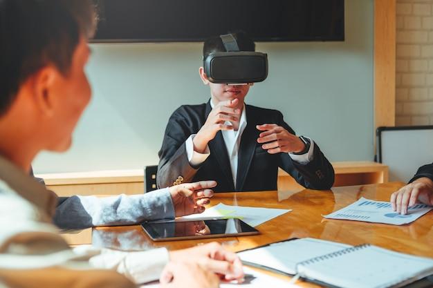 Reunião da equipe de negócios usando fone de ouvido do simulador de realidade virtual e desenvolvimento