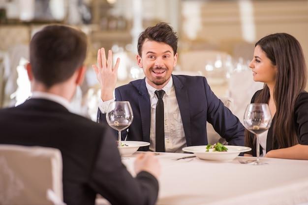 Reunião da equipe no restaurante, comendo e bebendo.