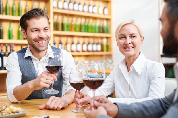 Reunião de cavists bem-sucedidos com taças de vinho tinto sentados à mesa e discutindo novos tipos de bebidas