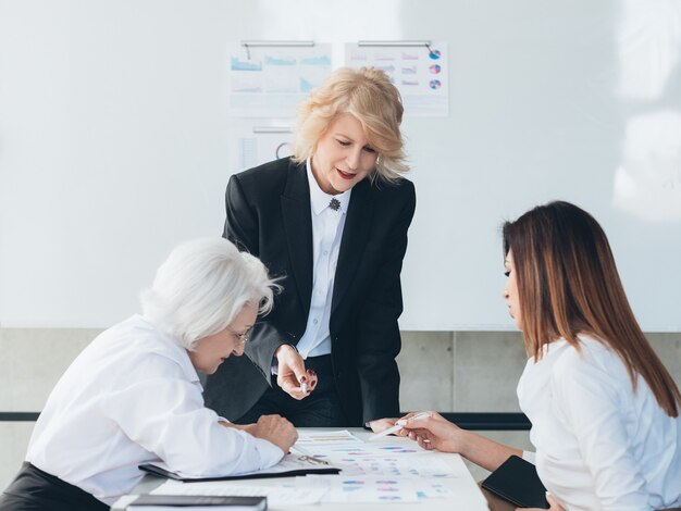 Reunião de equipe. mulheres de negócios com infográficos. análise da discussão da comunicação.
