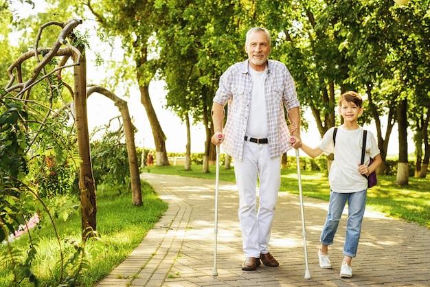 Reunião de família no parque. homem vai com caminhantes.