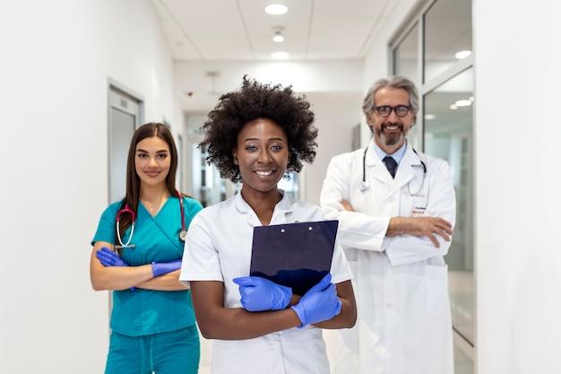 Reunião de médico e enfermeira de raça mista negra e branca. pessoal da clínica vestindo jaleco e estetoscópio