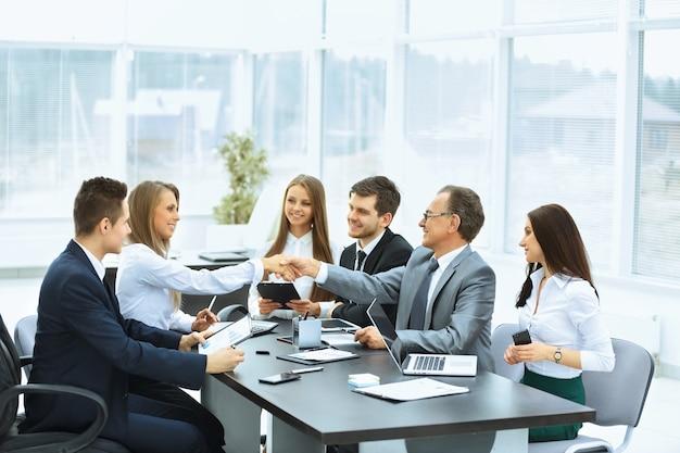 Reunião de negócios à mesa e aperto de mão de parceiros de negócios em um escritório moderno