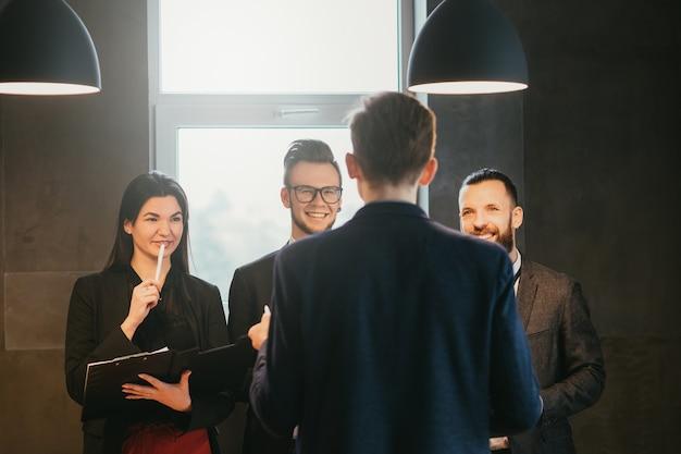 Reunião de negócios. funcionário do sexo masculino, compartilhando ideias de desenvolvimento de projetos com seus colegas. atmosfera profissional positiva.