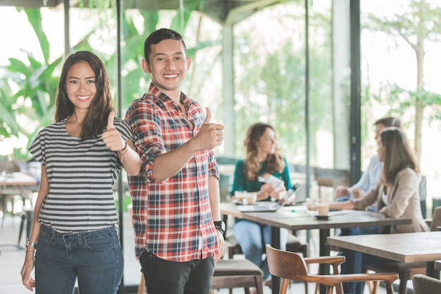 Reunião de negócios jovem na cafeteria. dois parceiros mostrando o polegar para cima