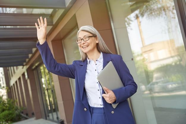 Reunião de negócios. retrato de uma mulher de negócios maduro alegre lindo vestindo terno clássico segurando laptop e acenando para alguém, de pé contra o exterior do prédio de escritórios. pessoas de negócio