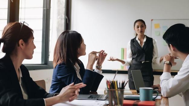 Reunião do consultor de negócios asiático para analisar e discutir a situação do relatório financeiro na sala de reuniões. consultor de investimentos, consultor financeiro e conceito de contabilidade