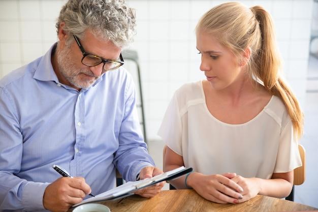 Reunião do empresário com o agente em co-working, escrevendo em papel, preenchendo e assinando o formulário de acordo