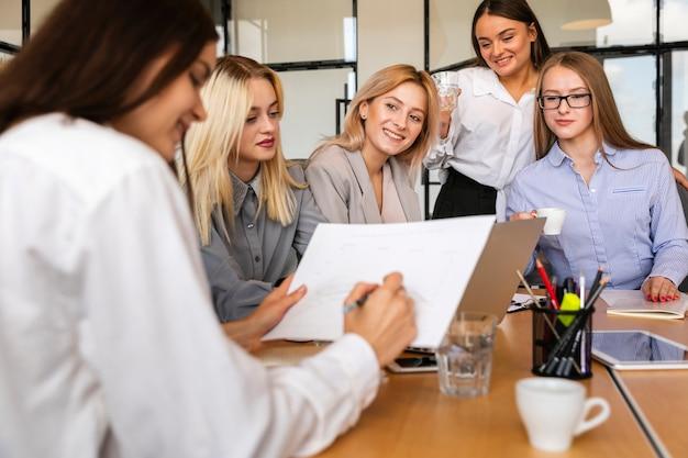 Reunião do grupo de mulheres vista frontal no escritório