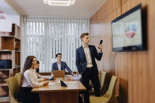 Reunião dos trabalhadores de escritório à mesa, olhando a apresentação com diagramas na tv