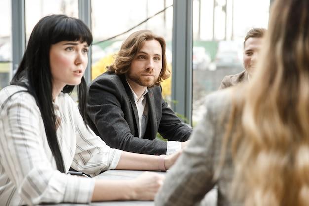 Reunião em andamento. dois funcionários de escritório estão olhando para o colega com expressão de surpresa no rosto
