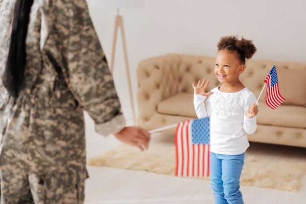 Reunião emocional. menina alegre e entusiasmada parecendo encantada ao ver sua mãe depois de ela passar algumas semanas em um campo de treinamento