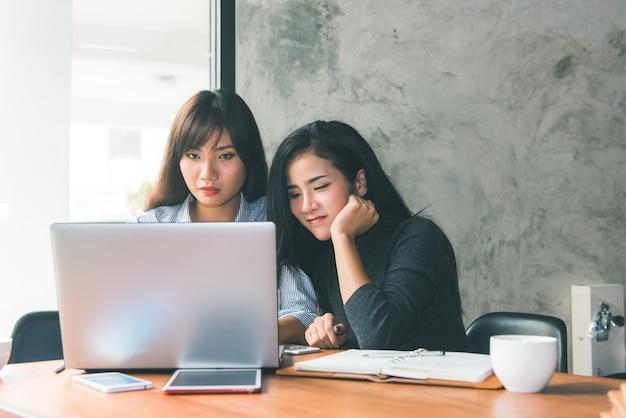 Reunião individual. duas jovens mulheres de negócios sentadas à mesa no café. a menina mostra informações do colega na tela do laptop. menina usando blogs de smartphones. reunião de negócios em equipe. freelancers trabalhando.