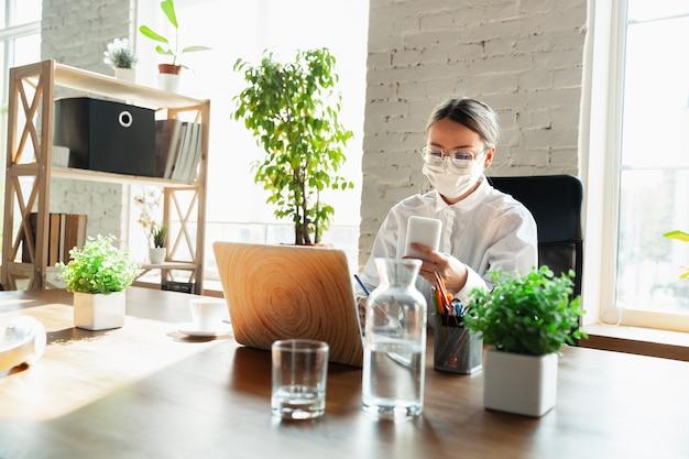 Reunião. mulher trabalhando sozinha no escritório durante a quarentena de coronavírus ou covid-19, usando máscara facial. jovem empresária, gerente fazendo tarefas com smartphone, laptop, tablet tem conferência online.