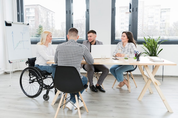 Reunião no escritório com mulher em cadeira de rodas