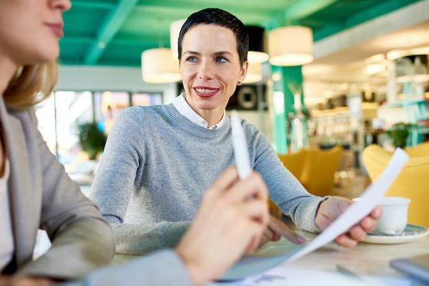 Reunião principal da mulher de negócio madura no café