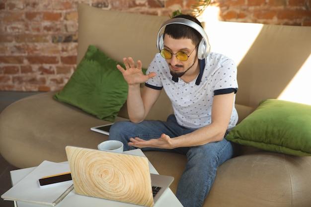 Reunião remota. homem que trabalha em casa durante a quarentena de coronavírus ou covid-19, conceito de escritório remoto. jovem empresário, gerente fazendo tarefas com smartphone, computador, tem conferência online.