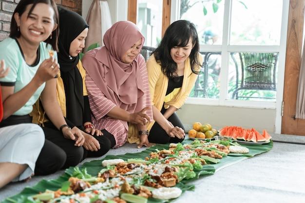 Reunião social da mulher asiática em casa almoçando
