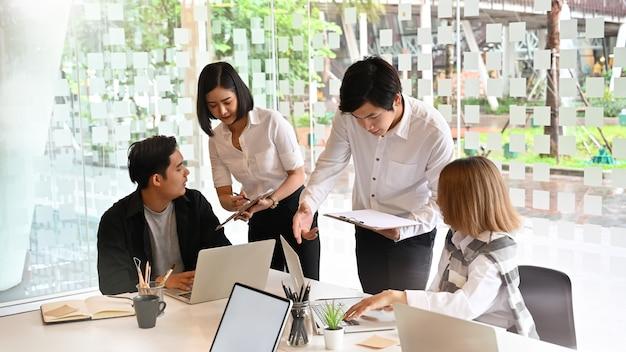Reunião startup da equipe do negócio com o papel do portátil e de original com tiro colhido.